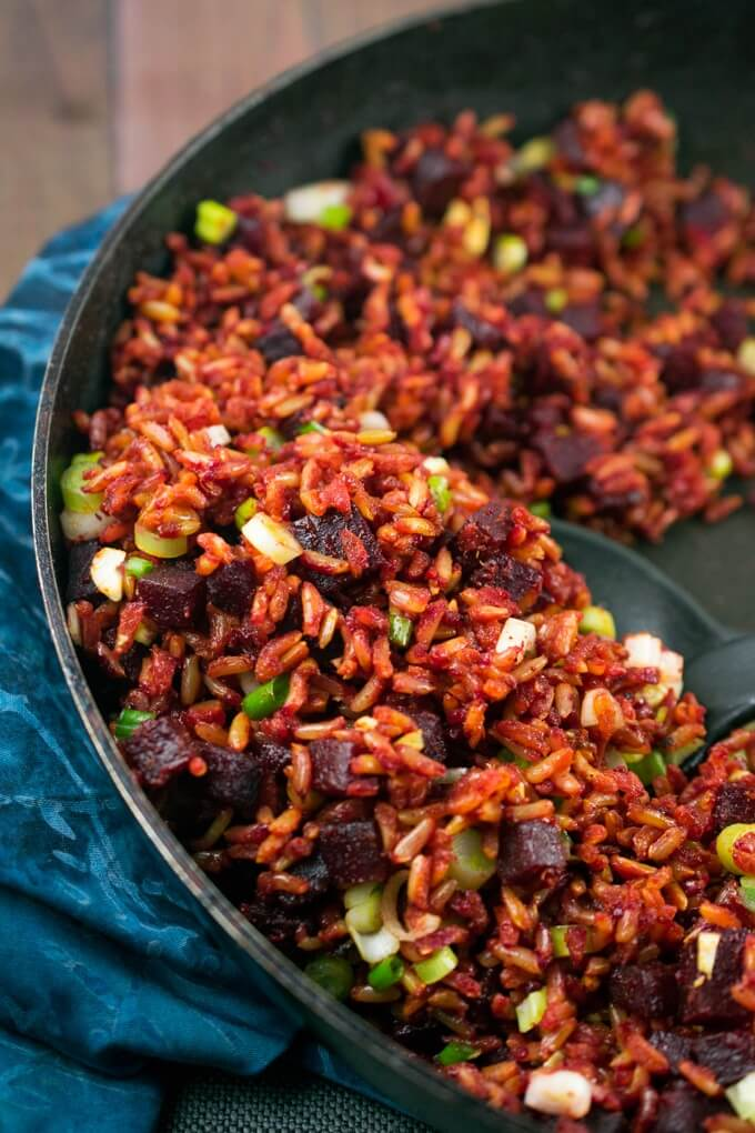 Beet fried rice mixed with scallions in a skillet on top of a blue tablecloth. A mixing spoon is scooping out a portion.