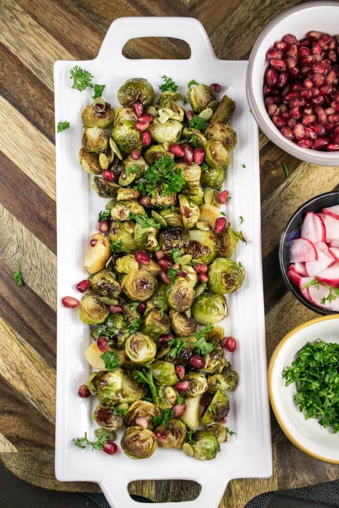 A plate of roasted Brussels sprouts arranged on a wooden serving platter next to bowls of pomegranate arils, sliced radishes, and parsley, and garnished with pumpkin seeds