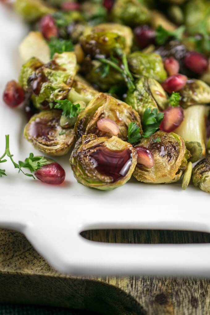Close-up of a few crispy and browned Brussels sprouts drizzled with pomegranate glaze and fresh pomegranate arils