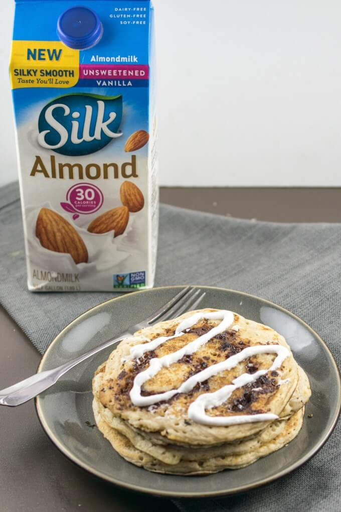 Stack of cinnamon swirl pancakes on a plate with a fork, with a carton of dairy-free almond milk in the background.