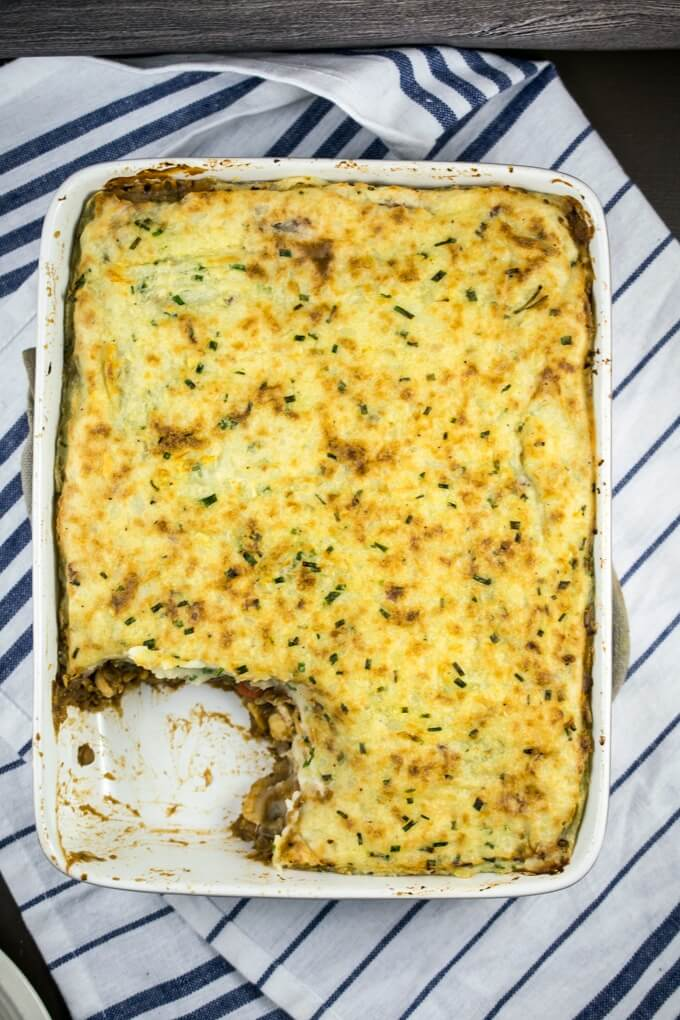 Overhead view of a baked vegan shepherd's pie with lentils, carrots and apple filling, with one piece missing.