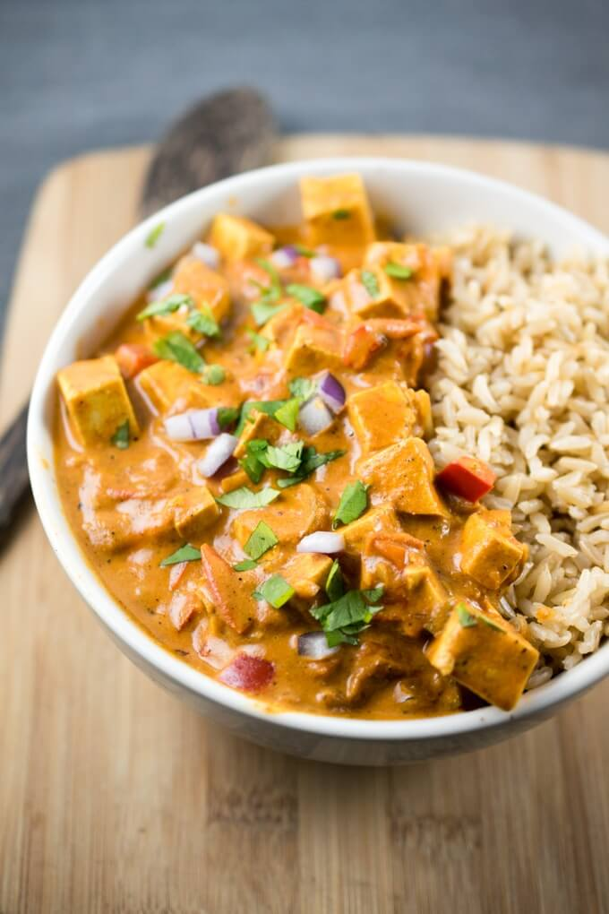 Slow cooker tofu tikka masala in a white bowl with brown rice and a brown wooden spoon in the background