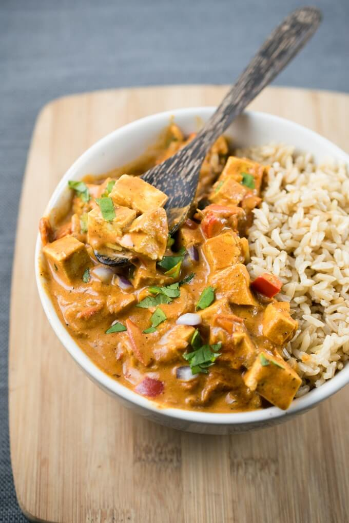 Overhead view of a bowl of vegan tikka masala curry with creamy coconut milk on a wooden cutting board, garnished with flecks of red bell pepper, cilantro and red onion