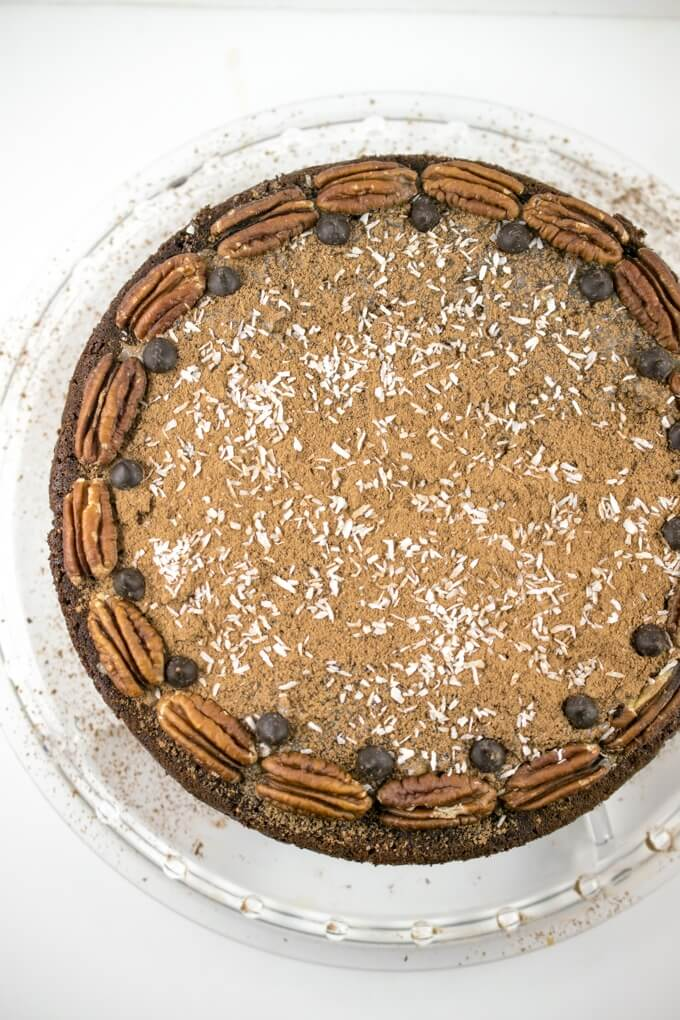 Overhead view of a vegan German chocolate cake on a clear cake stand decorated with cocoa powder, pecans, and chocolate chips.