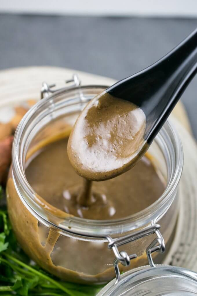 Black garlic vinaigrette being spooned out of a clear glass jar