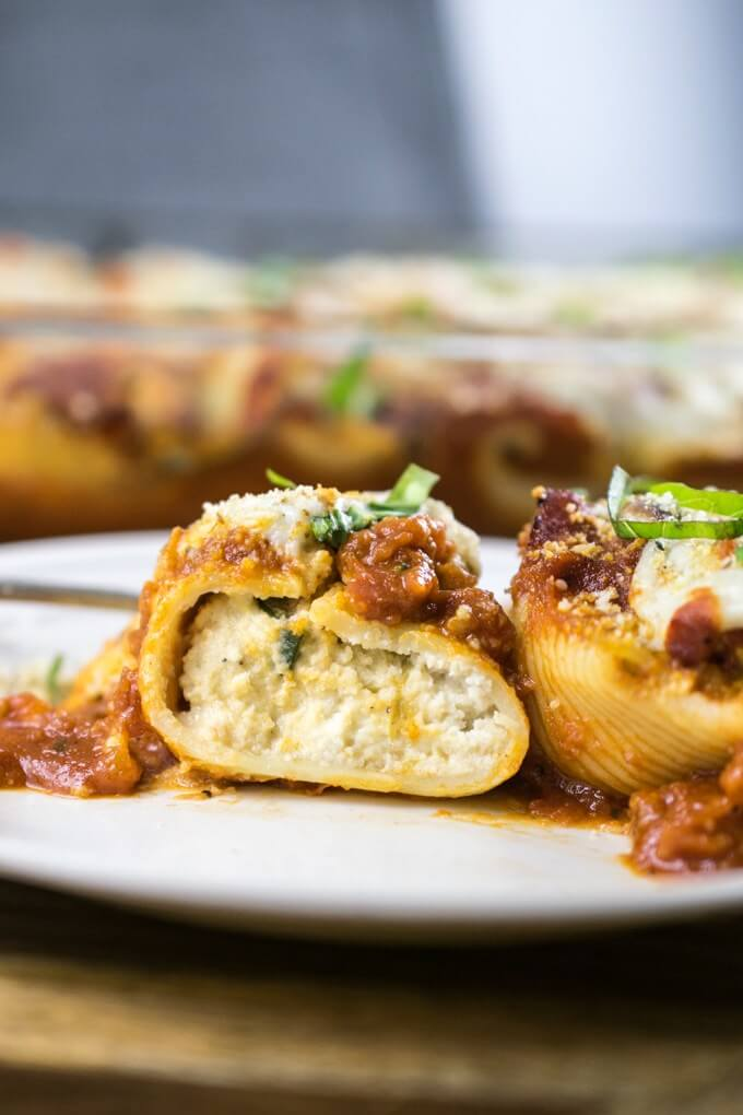 The interior of a vegan stuffed shell, with creamy almond ricotta and stir-fried cubed zucchini, topped with tomato sauce.