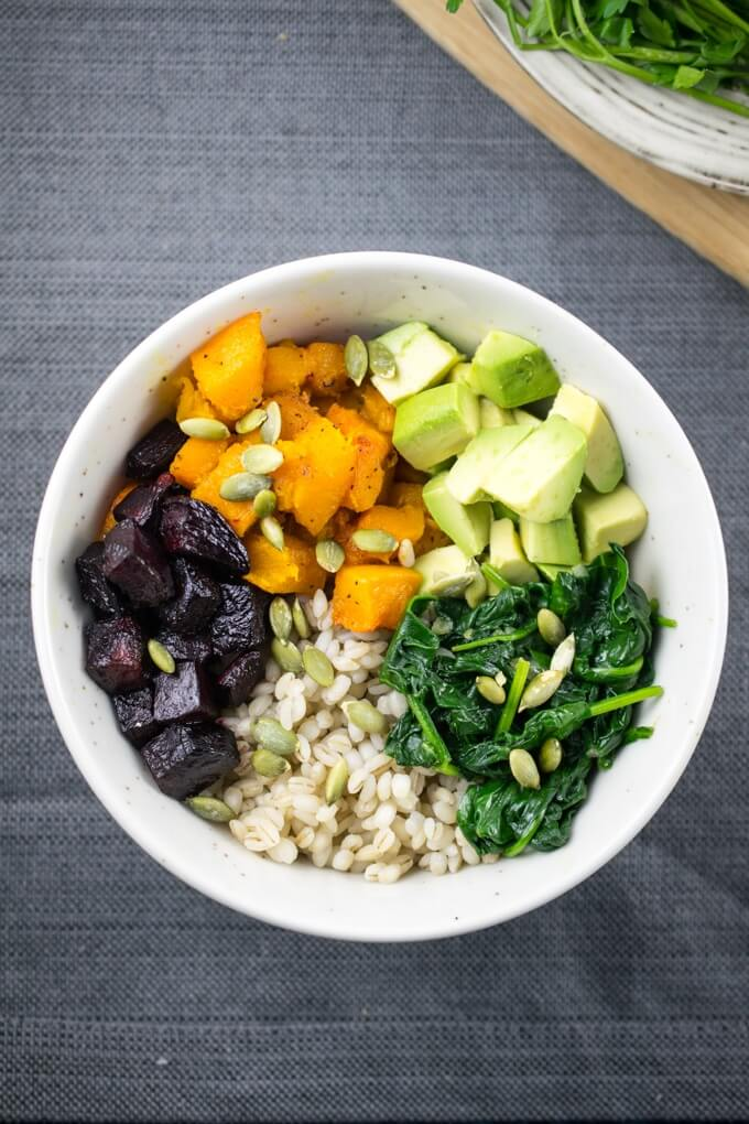 Overhead view of a winter roasted vegetable barley bowl with butternut squash cubes, beet cubes, ripe avocado, and cooked pearl barley.