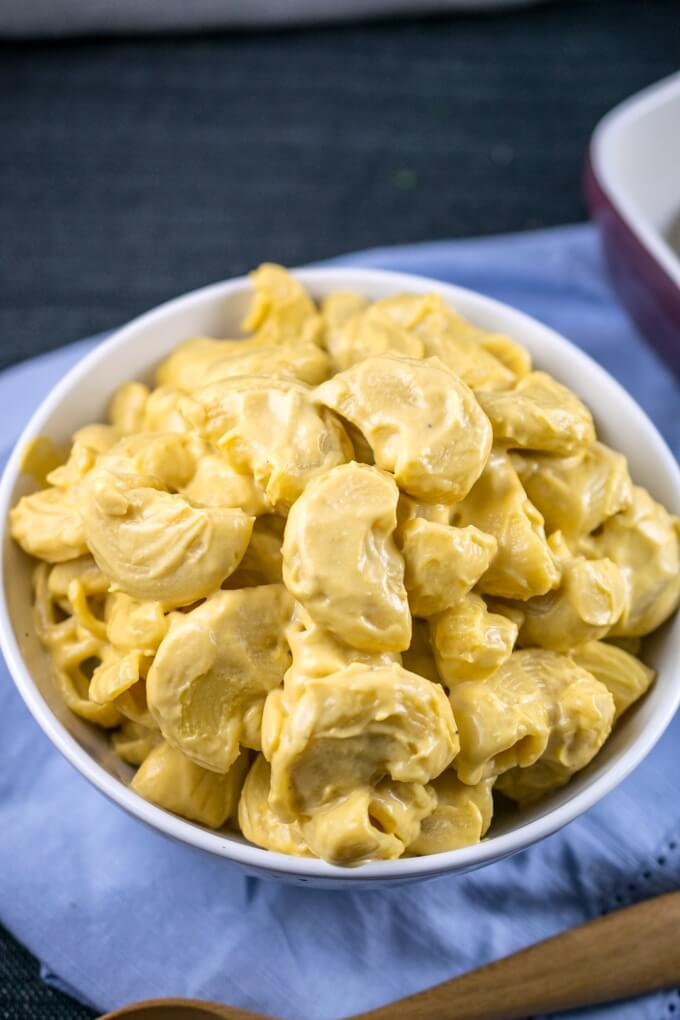 A bowl of vegan cauliflower mac and cheese, with the light yellow creamy sauce coating the pasta shells.