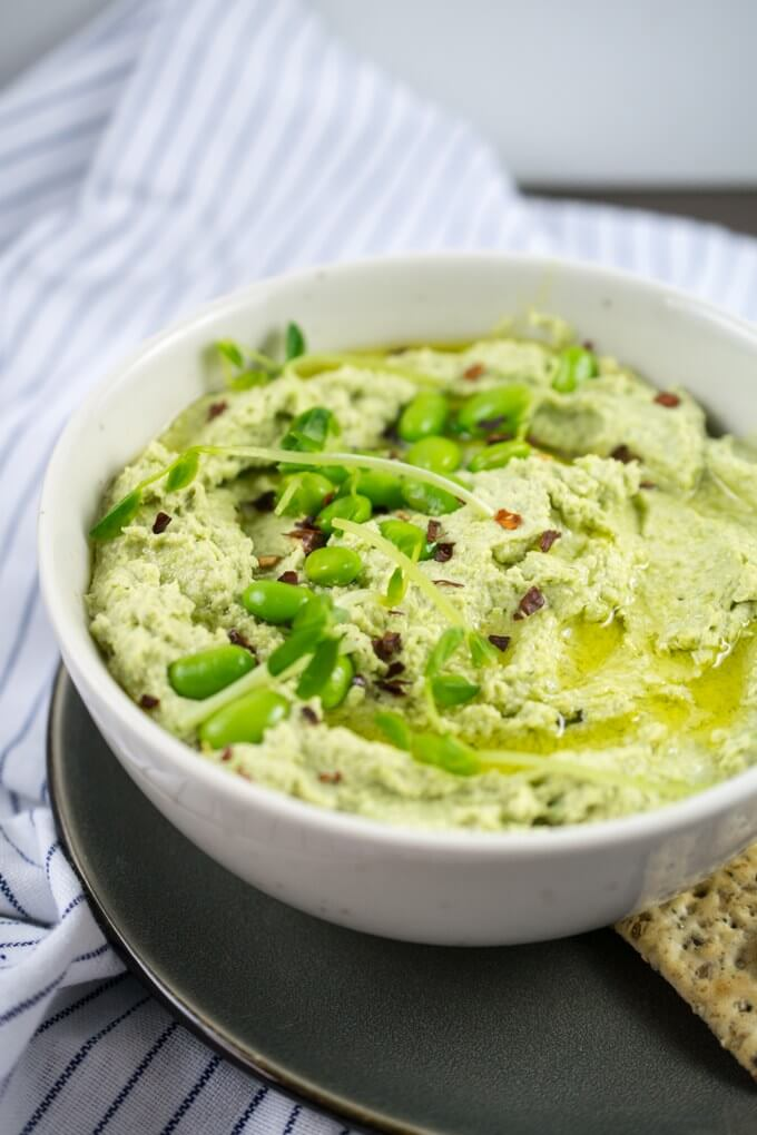 A bowl of green soybean hummus on a blue and white striped napkin with seeded crackers on a gray plate