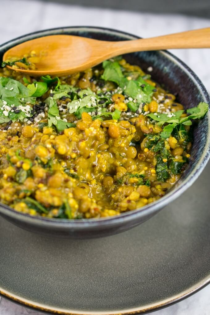 Closeup of the creamy texture of curried quinoa and lentils with bright green pieces of kale and a turmeric-yellow color evident.