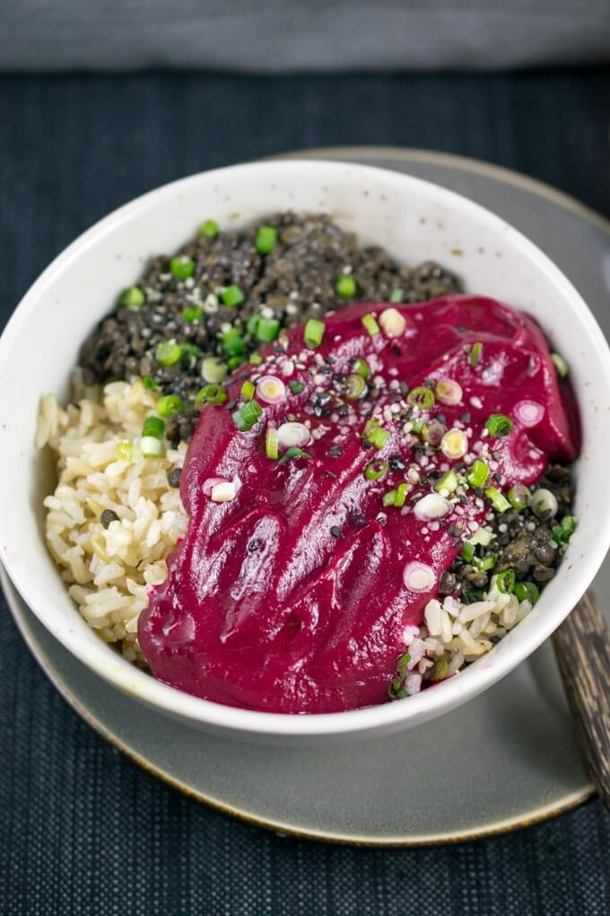 A ceramic bowl with Peruvian spiced beluga lentils, brown rice, and bright red beet puree