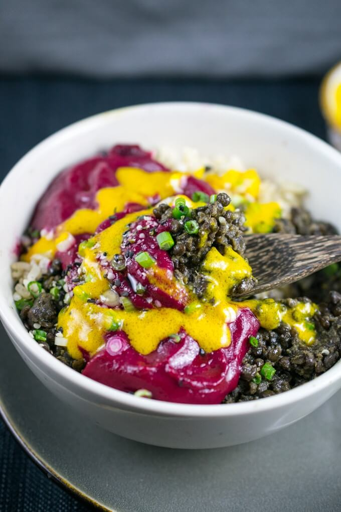 A bowl of Peruvian black lentils, beetroot sauce, and bright yellow aji amarillo chili oil drizzled over the top