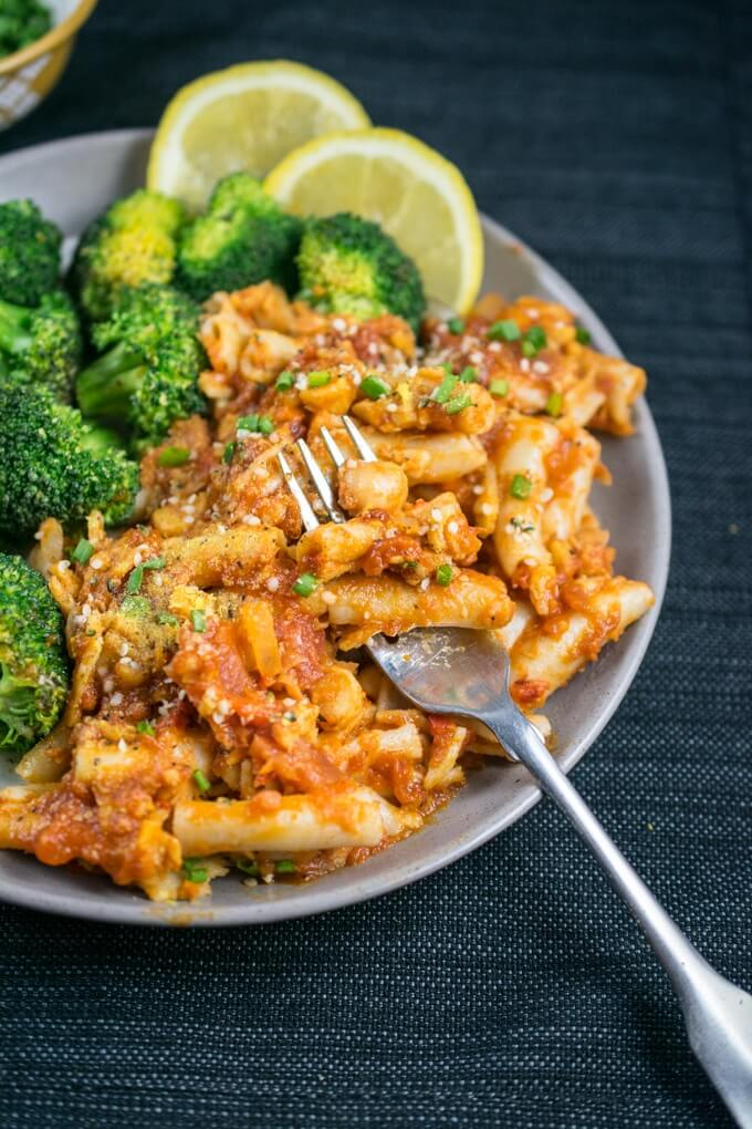 Red bell pepper and chickpea vegan pasta with lemon pepper broccoli, fresh herbs, and dairy-free parmesan garnish.