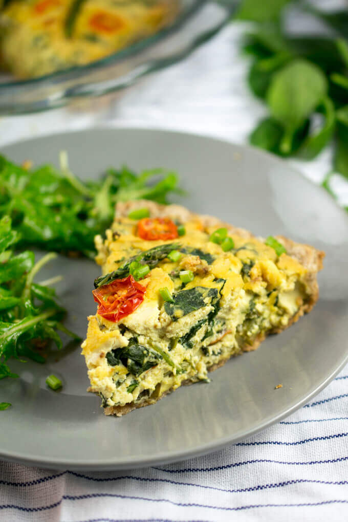 The creamy, pale yellow interior of a vegan tofu quiche, studded with asparagus, tomato, and spinach, with the rest of the quiche in the background.
