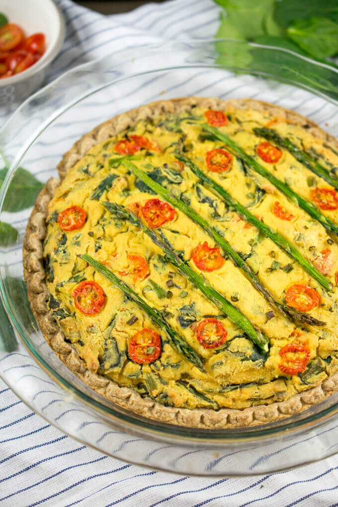 Eggless vegan quiche filling in a pie shell. The filling is creamy and light yellow, and the top of the quiche is garnished with a pattern of asparagus spears and roasted cherry tomatoes.