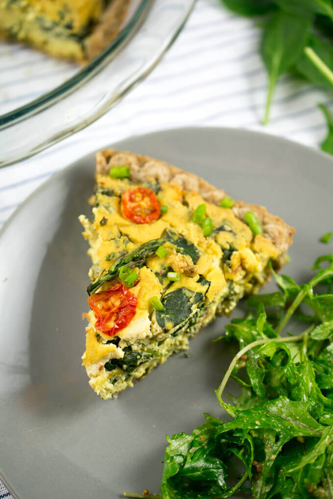 A slice of vegan quiche on a gray plate with a massaged kale salad. Pieces of spinach are visible inside the quiche and the quiche is garnished with fresh chives.