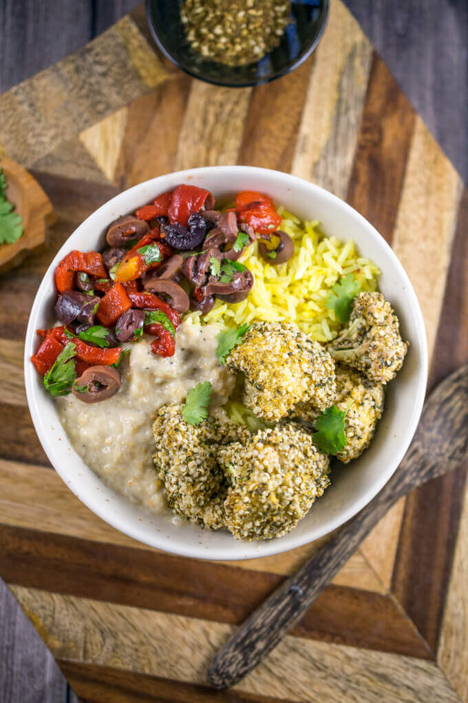 Overhead view of vegan za'atar cauliflower bowls on a wooden cutting board next to a wooden spoon.