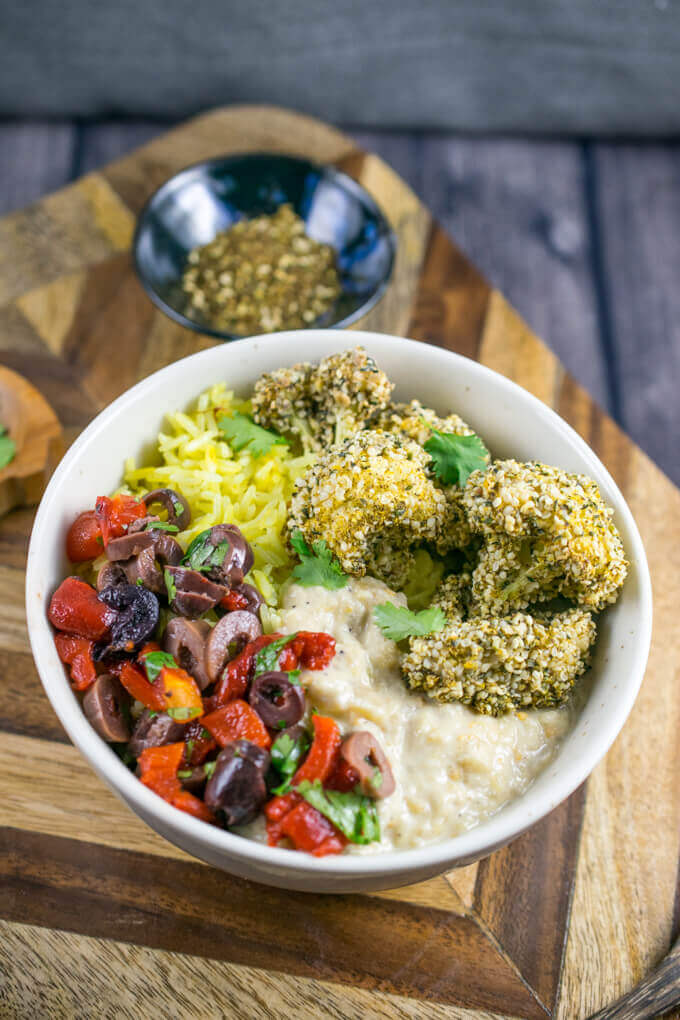 A ceramic bowl with creamy baba ghanoush, brightly colored olives and red pepper slices, cauliflower florets with a lightly browned seeded crust, sprinkled with za'atar, and a small scoop of golden colored saffron rice