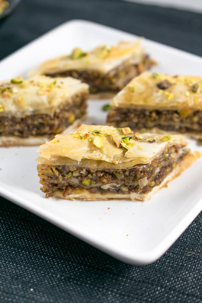 Four pieces of dairy-free baklava arranged on a square plate, garnished with chopped pistachios.