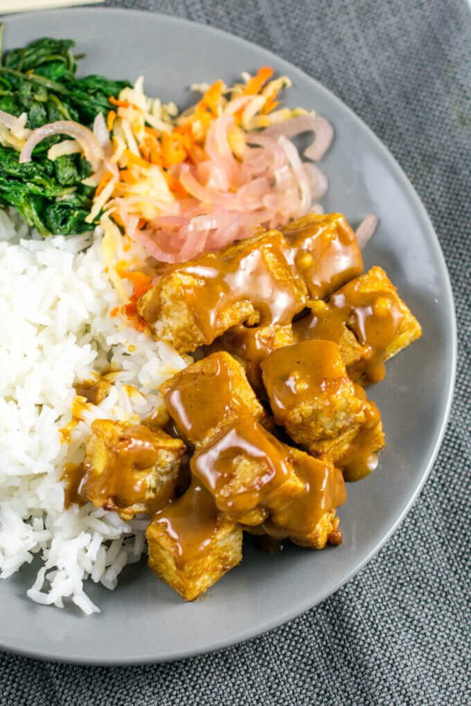 Crispy baked tofu cubes drizzled with shiny light brown peanut sauce, on a bed of white rice and pink slivers of shallot