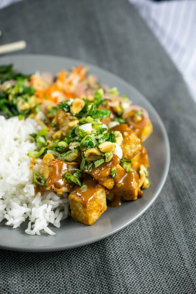 Baked crispy peanut tofu on a gray plate garnished with fresh green herbs and scallions