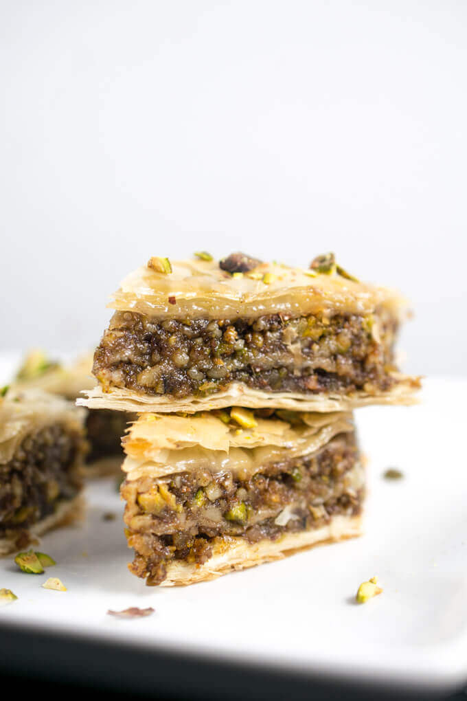 Two diamonds of vegan baklava stacked on top of each other on a white plate. Moist filling with flecks of walnuts and pistachios is visible.