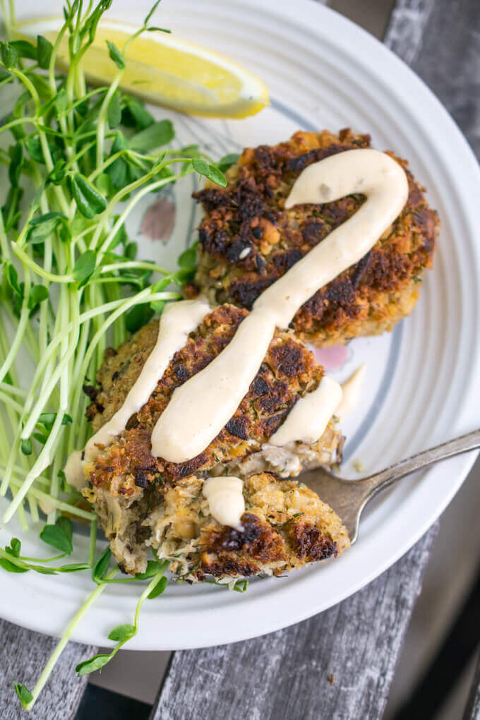 Overhead view of a vegan crab cake being cut into with a fork, with a wedge of lemon next to it