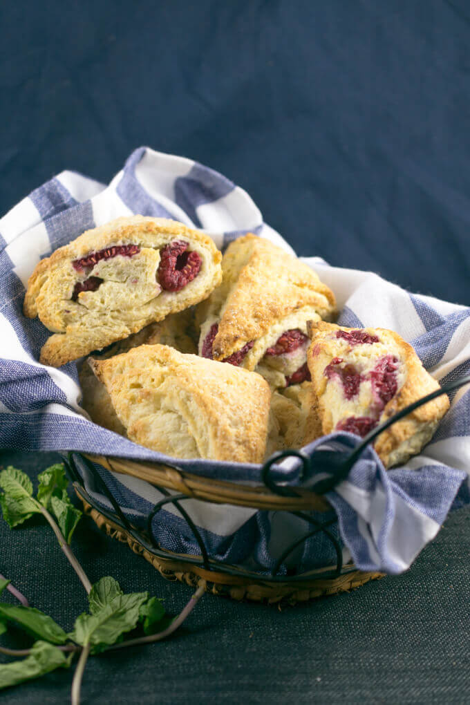 A basket of vegan scones with raspberries, garnished with fresh mint