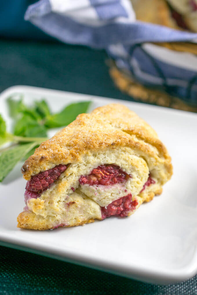 A single vegan scone on a plate, showing many layers of dough and fresh raspberries inside
