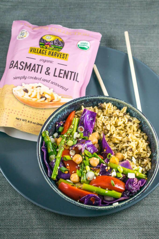 A bowl of chili lime veggie chickpea stir-fry on a blue plate next to a bag of Village Harvest Basmati & Lentil.