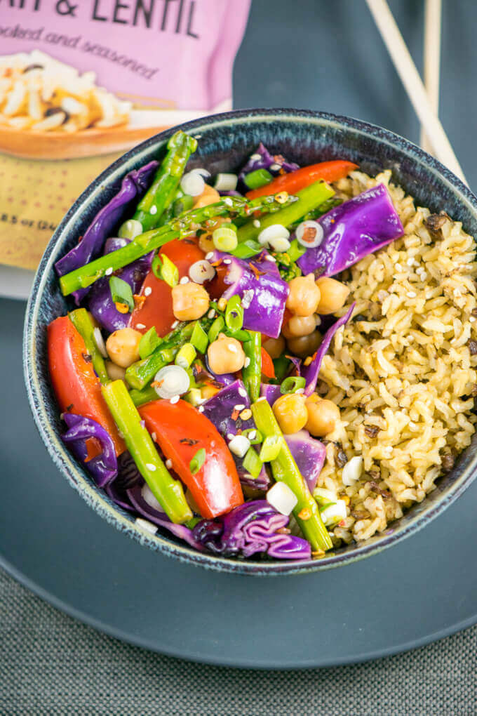 Overhead view of vegetable chickpea stir-fry in a bowl, with bright purple cabbage, asparagus, red bell pepper, chickpeas, and garnished with scallions and red pepper flakes next to brown rice.