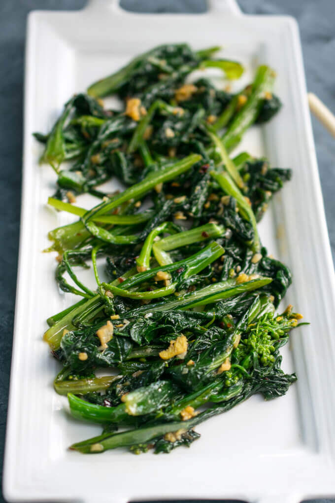 A plate of stir-fried choy sum pieces with visible bits of garlic and ginger.