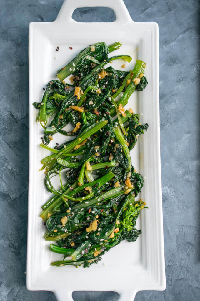 Overhead view of a plate of Chinese stir-fried gunsho (choi sum) garnished with sesame seeds