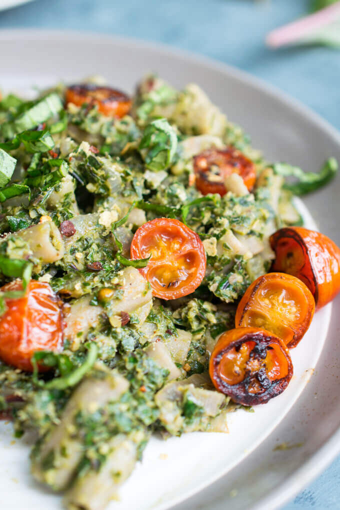 Close-up of a blistered cherry tomato with kale pesto penne pasta