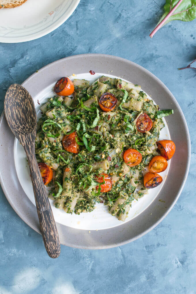 Overhead view of a plate of kale pesto penne pasta with halved tomatoes and a wooden spoon