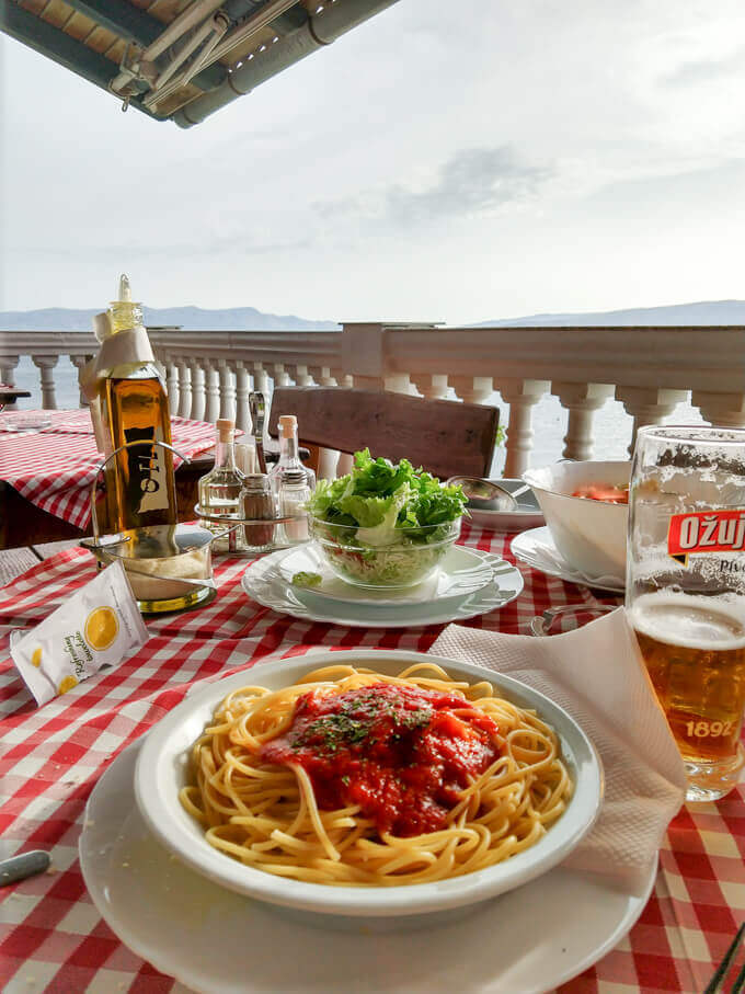 Table setting at a restaurant in Senj, Croatia with spaghetti napolitano, beer, and fresh salad