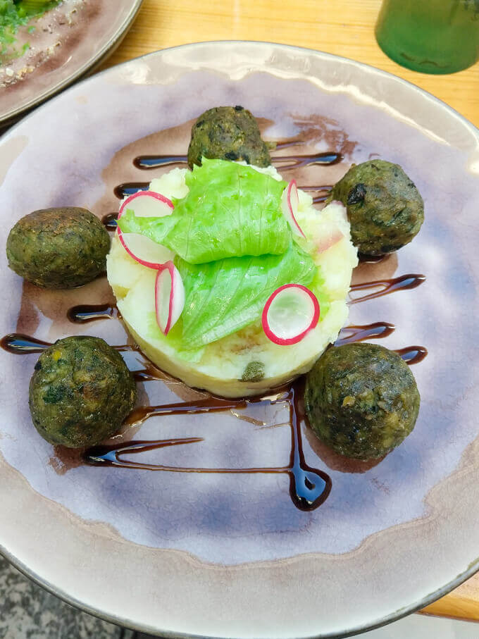 A plate arranged with spinach fritters, balsamic reduction, potato salad, lettuce and radishes in Šibenik, Croatia