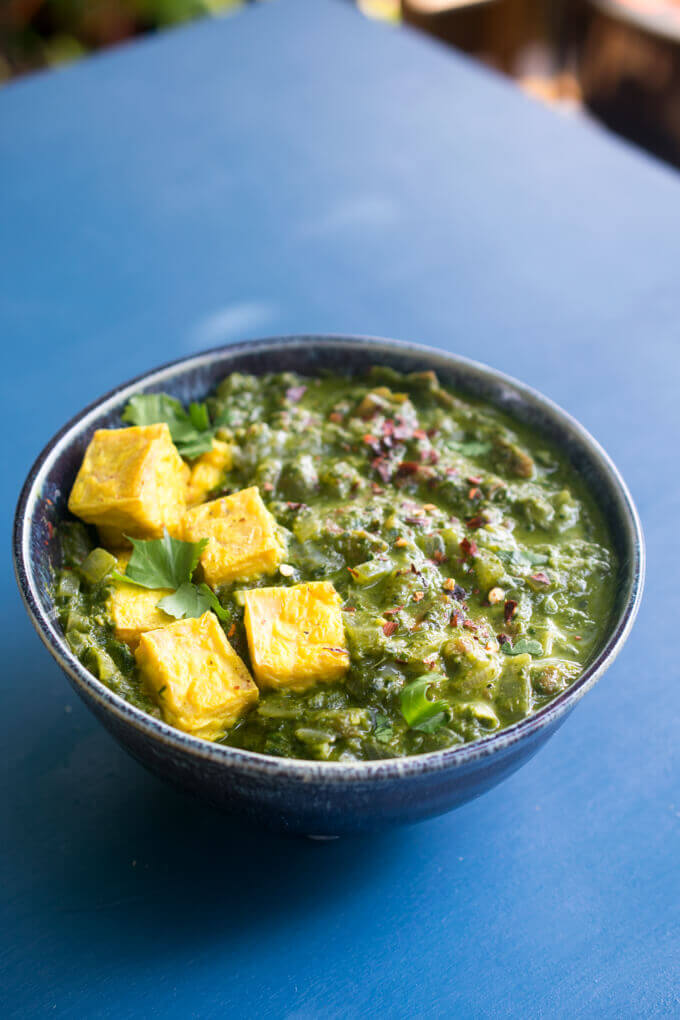 A bowl of vegan saag paneer on a blue background, garnished with fresh cilantro leaves.