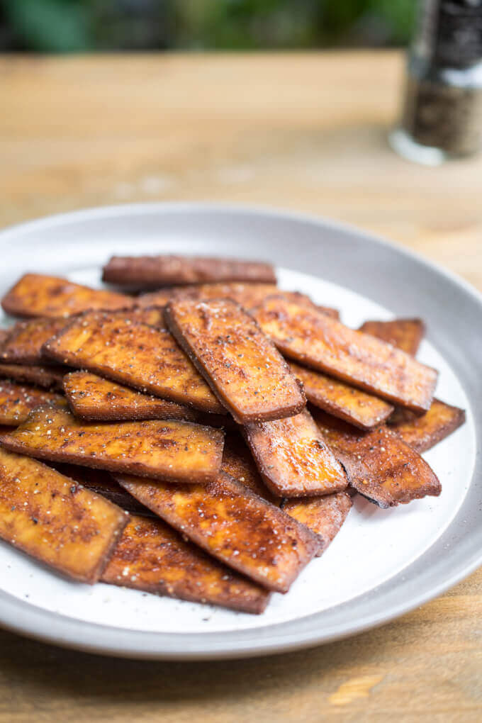 A plateful of vegan tofu bacon on a wooden table with a pepper grinder in the background
