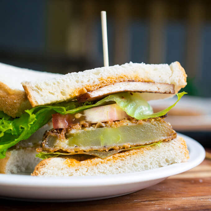 Vegan fried green tomato BLT sliced in half to show the delicious battered tomatoes, tofu bacon, fresh tomato, and lettuce.