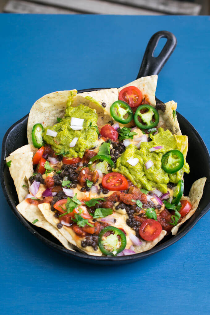 Overhead view of a pan with tortilla chips, vegan nacho cheese, tomatoes, jalapeno, dollops of guacamole, and diced red onions.