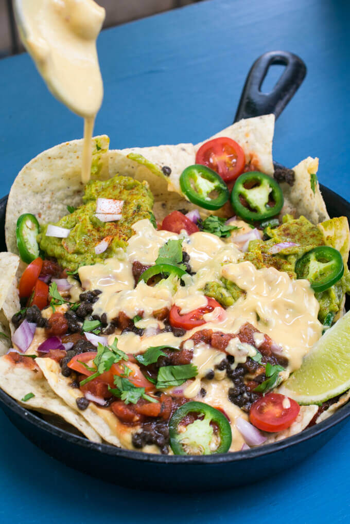A cast iron skillet full of nachos with vegan cashew queso being drizzled over them.