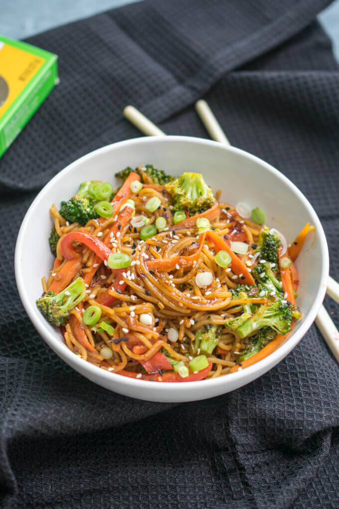 A bowl of noodles in garlic sesame sauce with sliced scallions, broccoli, bell pepper, and sesame seeds.