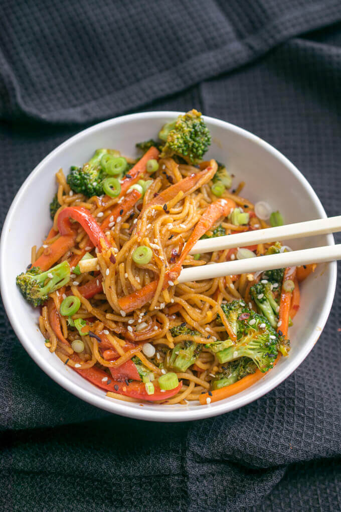 A bowl of vegan garlic sesame noodles with two chopsticks