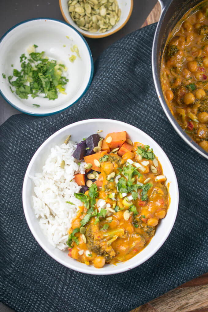 A bowl of one pot pumpkin curry with rice, and smaller bowls holding garnishes of cilantro and pumpkin seeds, with the big pot of curry in the background