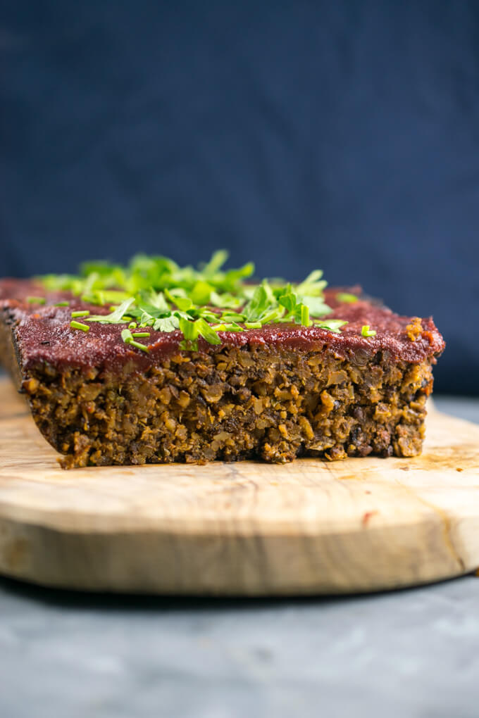 Front view of vegan walnut lentil meatloaf, with a shiny red glaze and chopped parsley on top