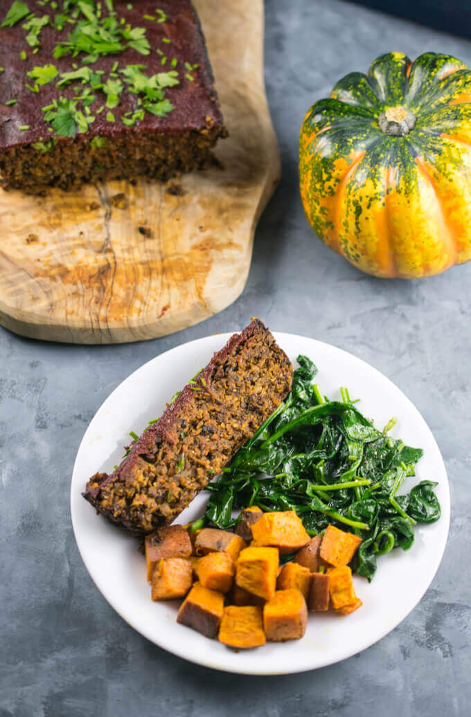 A slice on lentil loaf on a plate with sauteed spinach and roasted cubed sweet potato, with the full vegan meatloaf platter and a pumpkin in the background