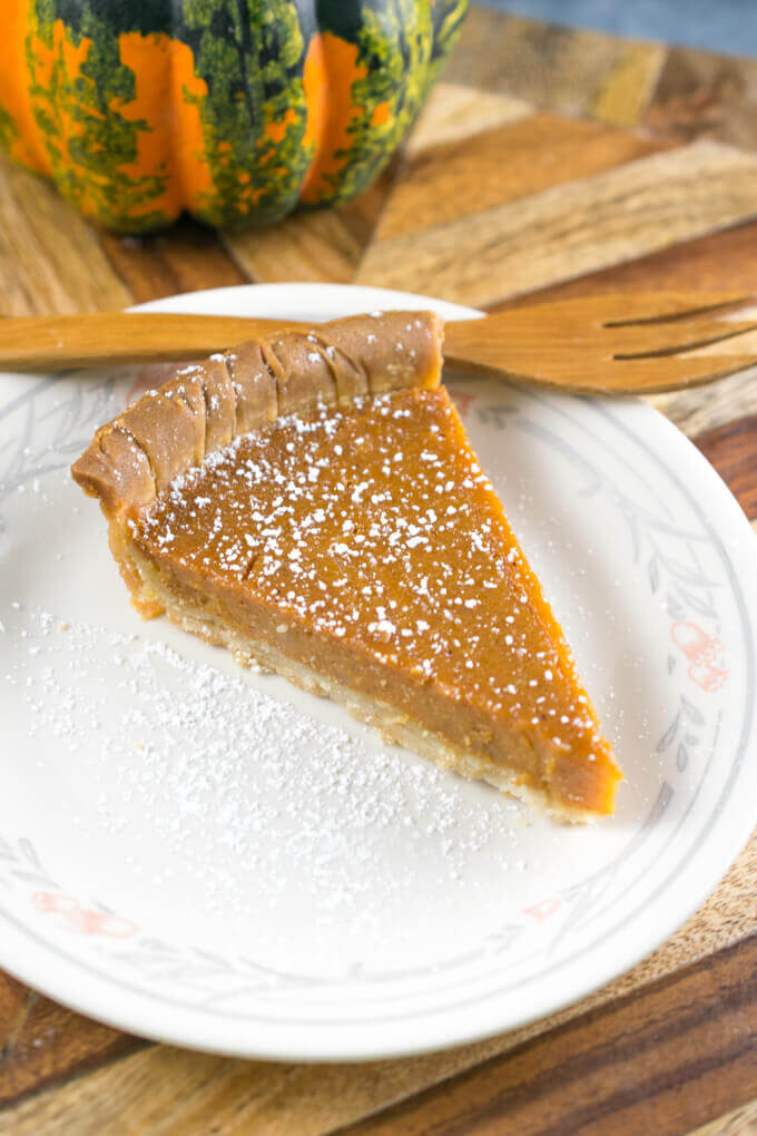 A slice of vegan sweet potato pie on a plate, dusted with powdered sugar, next to a wooden fork