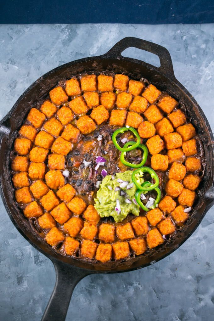 Overhead view of a sweet potato hotdish with a creamy black bean layer layered with sweet potato tater tots, with a dollop of guacamole and 4 sliced jalapenos on top
