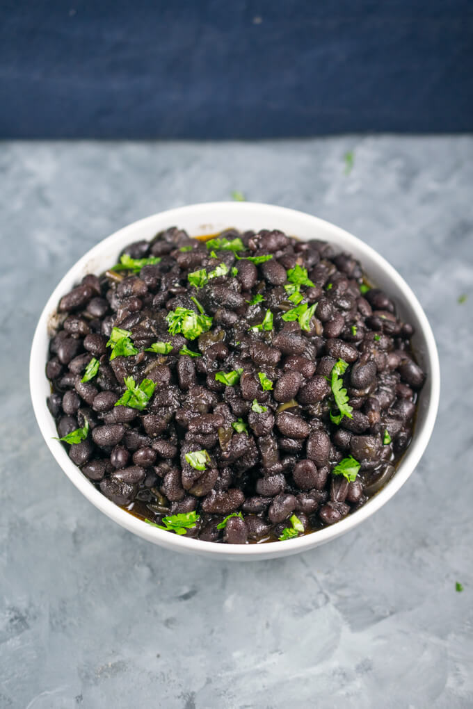 A white bowl of Instant Pot black beans on a grayish blue background, garnished with chopped up fresh cilantro